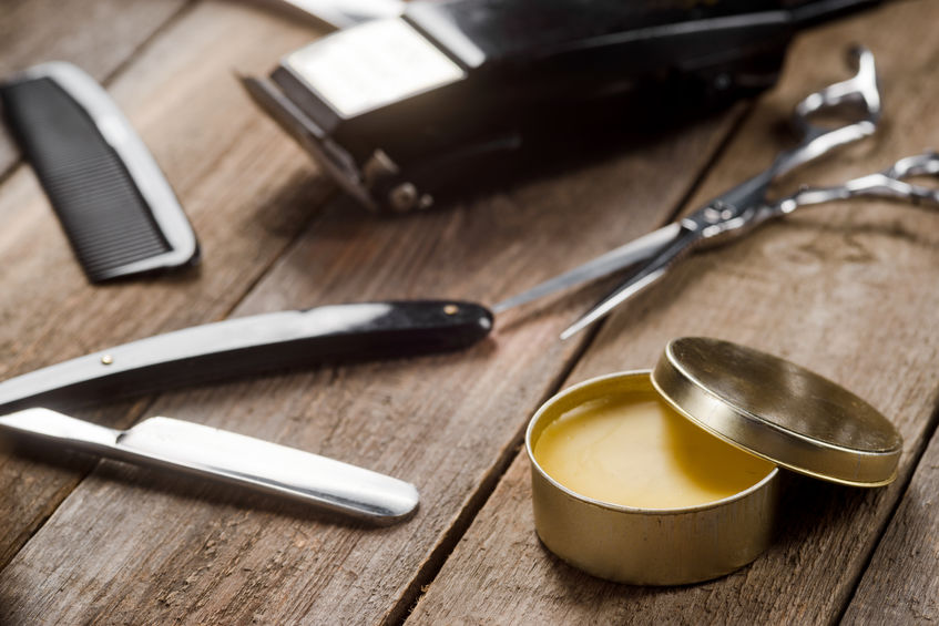 Wax, barber scissors, a straight razor, a comb on the wooden surface
