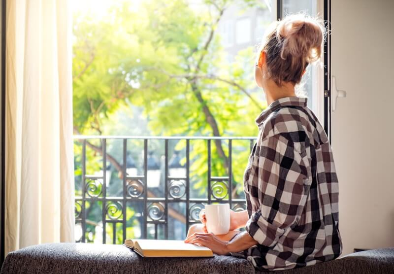 young woman looking through the window while holding a cup of coffee and book