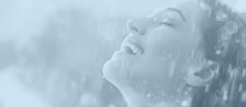 woman smiling while rain is falling on her face